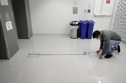 A man places safe distancing floor markings near an elevator on the campus of Boston University. But will students comply?