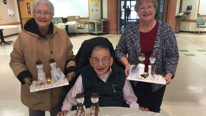 Centerpieces were given to Commission on Aging & Disabilities members at the holiday breakfast by the Bureau of Aging & Disabilities. COAD members are, Val Cioeff, seated, Senior Inclusion Program; Hermine Saunders, left, COAD Chair; and Carol Wheatley, representing Westminster.