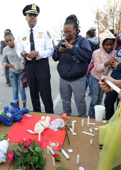 Members of the community as well as Maj. Melvin T. Russell, attend a vigil for Monae Turnage, a 13-year-old who was fatally shot.