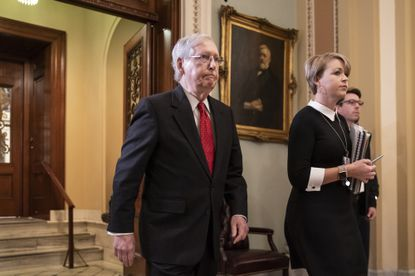 Senate Majority Leader Mitch McConnell steps out of the chamber during the start of the impeachment trial of President Donald Trump on Jan. 21, 2020.