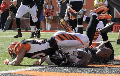 Cincinnati Bengals cornerback Leon Hall, top, defends against Ravens wide receiver Kamar Aiken on a fourth-down play in the first quarter.