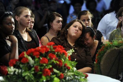 Jessica Dickerson (facing camera) bends her head toward her sister Brooke Dickerson, right, at the funeral service for their girl scouting friend, LaRelle Ashlyn Amos.