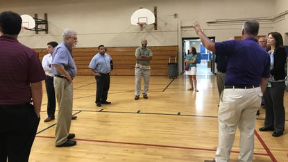 Tom Hill, the director of middle schools for CCPS, gives a tour of the West Middle School gymnasium to the Redistricting and School Closure Committee Thursday, Aug. 9, 2018.