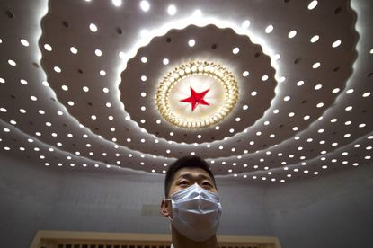 A Chinese security official wearing a face mask stands guard after the opening session of China's National People's Congress (NPC) at the Great Hall of the People in Beijing, Friday.