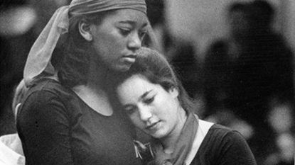 Shanie Harris, left, and Ellen Barth of The Young Columbians embrace during a musical retrospective of American cultural change performed at The Mall in Columbia for the 13th-annual African-American History Celebration in 1994.