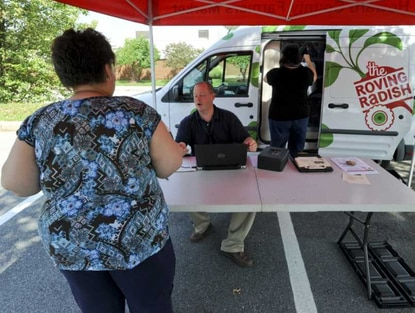 Roving Radish market manager James Zoller chats with a customer while Howard County Food Policy director Kelly Dudeck retrieves a food kit from the refrigerated truck.