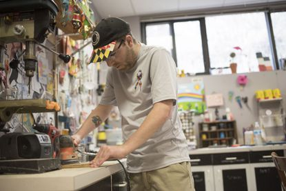 Tom sands wood in the art room at Baltimore's Itineris Foundation, which helps adults with autism develop real-world skills and find employment.
