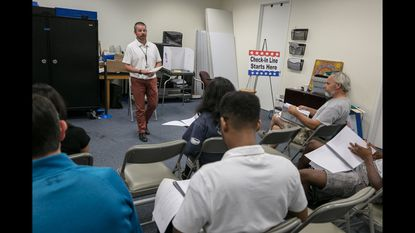 As local election officials in Maryland grapple with how to implement Republican Gov. Larry Hogan's edict to hold a traditional election this fall, they're turning to the option of consolidating polling places. In this 2018 photo, Howard County elections board director Guy Mickley goes over some guidelines with Election Day workers in Columbia.