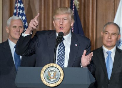 """<font color=""""#000000"""">US President Donald Trump makes remarks prior to signing an Energy Independence Executive Order at the Environmental Protection Agency Headquarters on March 28, 2017 in Washington, DC. The order reverses the Obama-era climate change policies. US Vice President Mike Pence look on from left and EPA Administrator Scott Pruitt looks on from (Photo by Ron Sach-Pool/Getty Images) </font>"""