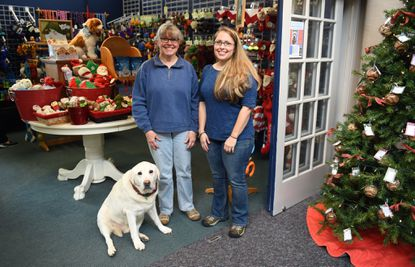 Owners Kate Bowman, right, Ann Bowman and Clipper, a 14-year old yellow lab for whom the store is named, at Clipper's Canine Cafein Savage Mill.