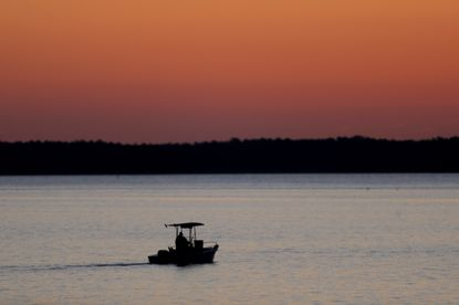 In this May 14, 2020 file photo, a small boat chugs along the Honga River near the Chesapeake Bay as the sky lights up at sunrise, in Fishing Creek, Md. Researchers are predicting a slightly smaller-than-average oxygen dead zone in the Chesapeake Bay this year.