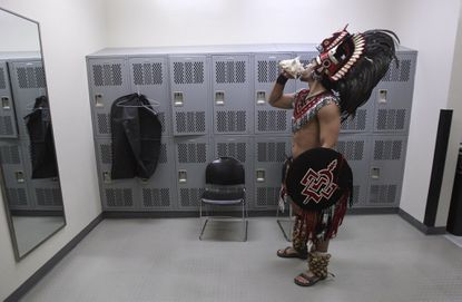 Richard Guzman, 19, a San Diego State sophomore, practices blowing his conch shell as gets ready to be the SDSU Aztec Warrior mascot while in a men's room.