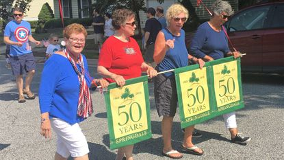 Original Springdale homeowners, from left, Peggy Concepcion, Shirley Gutberlet, Nancy Walton and Helen Shanks carry banners marking the community's 50th anniversary during the children's July 4th parade.