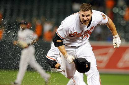 Chris Davis #19 of the Baltimore Orioles runs away from his teammates after driving in the game-winning run with a single in the 13th inning against the Boston Red Sox at Oriole Park at Camden Yards on September 15, 2015 in Baltimore, Maryland. Baltimore won the game 6-5.