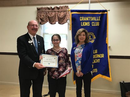 Katie Pedulla, one of two 2019 winners in the American Heritage, Preservation, & Patriotism Essay Contest, receives her award from the district governor, Gerry Beachy, left, and the district essay contest chair, Sandy Moore, right. Sophie Louis was the other winner.