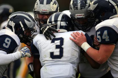 Howard senior Najee Savage (center), seen celebrating with his teammates in this file photo, ran for 157 yards and a touchdown in the Lions' 28-7 win over Perry Hall in the first round of the regional playoffs on Friday.