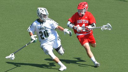 Loyola Maryland defenseman Foster Huggins keeps the ball from Boston University attackman Chris Gray. Huggins leads the nation in caused turnovers after his third ACL operation in five years.
