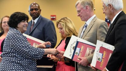 Harford County Public Schools Superintendant Barbara Canavan, left, shown greeting new school board members at their 2015 swearing in, presented her proposed $466.1 million unrestricted operating budget for the next school year to the board Monday evening.