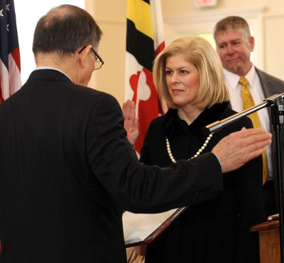 Laura Neuman, who was selected as Anne Arundel County Executive yesterday, is sworn in at the Anne Arundel County courthouse Feb. 22 by Clerk of the Court Robert P. Duckworth, left.