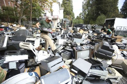 An e-waste worker in Nevada County, California wades through a sea of electronic items dropped at Mount St. Mary's School for their annual recycling event on Oct. 10, 2020. (Elias Funez/The Union via AP)