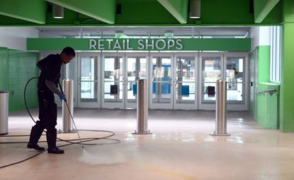 A pressure washer cleans an entranceway to Towson Town Center on Friday. The mall and other indoor malls in Maryland were shut down indefinitely last week.
