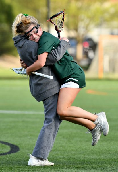 St. Paul's Frannie Hahn, a sophomore, gets a big hug after her three goals helped St. Paul's beat No. 1-ranked McDonogh, 16-9, handing the Eagles their first regular-season loss since 2009. April 21, 2021 p6