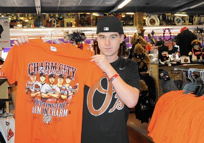Colin Maskavich, of Abingdon, an employee of Poor Boys Sports, holds a piece of Baltimore Orioles merchandise on sale at the Abingdon store Monday.