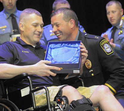 Carroll County Sheriff Jim DeWees awards the sheriff's department's first Purple Heart Award to Cpl. Brant Webb who was seriously injured in a car crash while on duty during the Carroll County Sheriff's Office Employee Awards Ceremony at Carroll Community College in Westminster Wednesday, March 30, 2016.