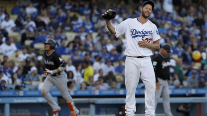 Dodgers starting pitcher Clayton Kershaw doesn't watch as Miami Marlins Miguel Rojas rounds the bases after hitting a three-run homer in the fifth inning at Dodger Stadium on Wednesday.