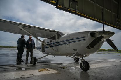 Eric Melancon, left, chief of staff for the Baltimore Police Department and Ross McNutt, founder of the Persistent Surveillance Systems, look over the plane that started flying over Baltimore last month.