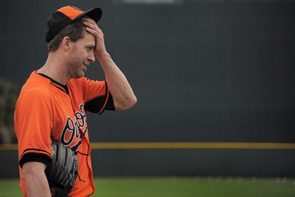 Orioles pitcher Mark Hendrickson wipes his brow during spring training.