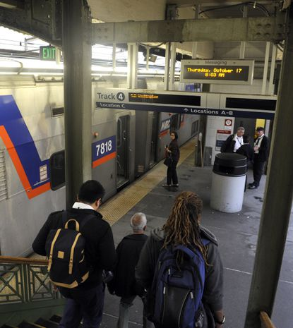 Passengers walk down stairs at Penn Station, where they will board a MARC train to Washington D.C.
