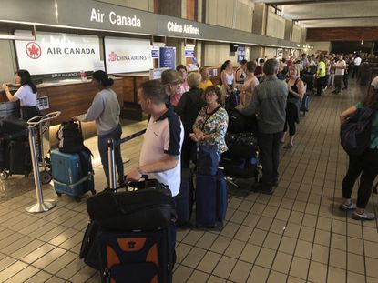 Passengers from an Australia-bound Air Canada flight diverted to Honolulu stand in line at the Air Canada counter at Daniel K. Inouye International Airport to rebook flights on July 11, 2019.