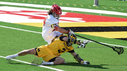 Michigan's Kevin Mack (2) chases after the ball while Maryland defender Nick Grill (54) tries to stop him in the 2nd quarter. The University of Maryland Terrapins host the Michigan Men's Lacrosse team in College Park on Saturday, February 20, 2021.