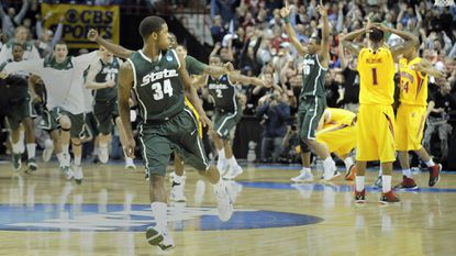As Michigan State's Korie Lucious, front, looks back, his teammates charge the floor and Maryland players look on after the game-winning shot.
