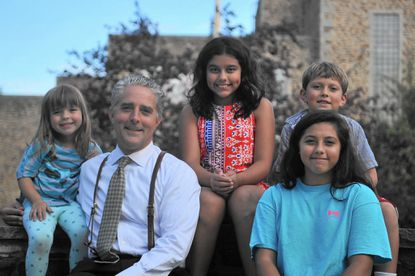 Steve Prumo poses with his children outside of Towson High School, including Rosa, 13, Sofia, 10, Rafael, 7 and Olivia, 4. Prumo is among those advocating that Baltimore County build a new Towson High by 2022.