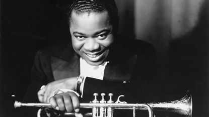 Jazz musician Louis Armstrong poses with his trumpet and his signature smile in 1931.
