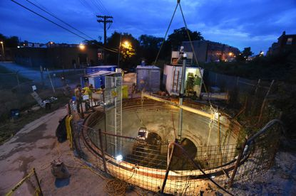 Workers with Bradshaw Construction work on drilling a 2,500-foot tunnel for a new 36-inch sewer pipe in West Baltimore.