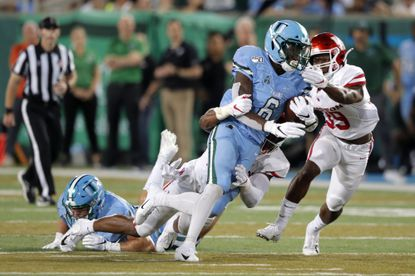 Tulane running back Corey Dauphine (6) carries as Houston cornerback Shaun Lewis (39) pursues in the second half of an NCAA college football game in New Orleans, Thursday, Sept. 19, 2019. Tulane won 38-31. (AP Photo/Gerald Herbert)