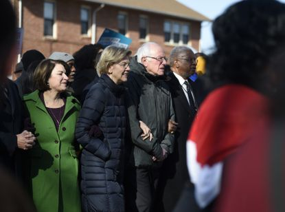 Democratic presidential candidates Elizabeth Warren and Bernie Sanders link arms during a Martin Luther King Jr. Day march on Monday, Jan. 20, 2020, in Columbia, S.C.
