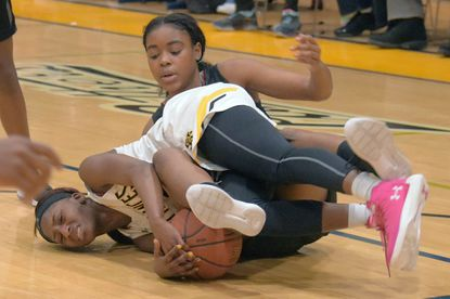 St. Frances guard Delicia Pinnick, left, scraps on the floor with McDonogh forward Sijay Matsinye, who causes a jump ball call that goes to the Panthers during a key matchup Jan. 19 at John & JoAnne Phelps Gymnasium. St. Frances won, 68-54.