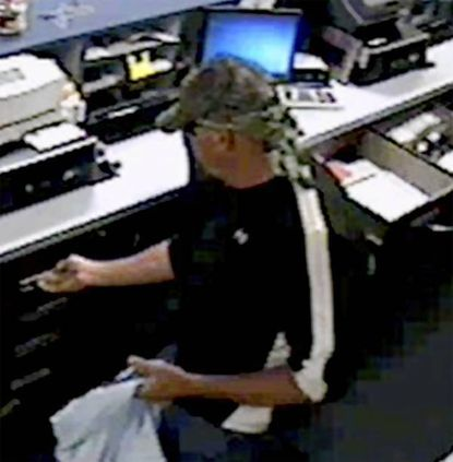 A robber goes through cash drawers at the Liberty Bank inside Harford Mall on Friday morning.