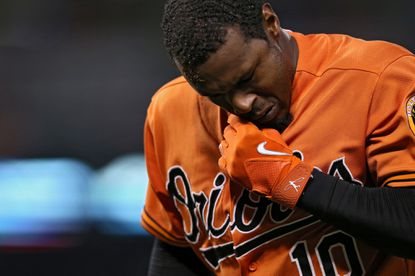 Orioles' Adam Jones wipes his face after being involved in a collision at first base against the Washington Nationals in the fifth inning at Camden Yards on July 11, 2015 in Baltimore.