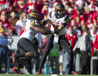 Maryland quarterback C.J. Brown hands the ball off during the first quarter against at Camp Randall Stadium.