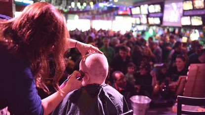 A child gets his head shaved in front of the crowd gathered for the 2018 St. Baldrick's event, a childhood cancer fundraiser, at Looney's Pub in Bel Air.