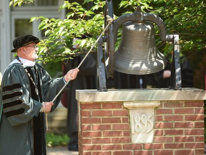 Roger Casey, outgoing president of McDaniel College, rings a bell as graduates begin their processional across campus to the 149th commencement ceremony in 2019.