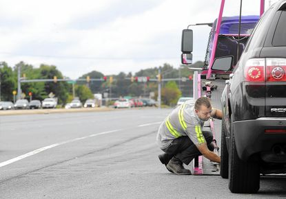 Brad Kauffman, of Green's Garage in Hampstead, demonstrates the hazards of roadside towing along eastbound Route 140 in Westminster on Wednesday.
