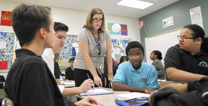 """English teacher Wendy Jensen discusses themes of """"Things Fall Apart"""" with students Alexander Bonilla, Brandon Hill, Josh Brunk and Thomas Copeland at Chesapeake Science Point."""