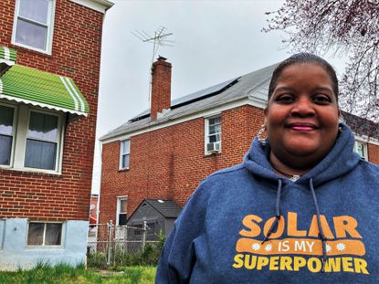 Kimberly Armstrong, Maryland program director for Solar United Neighbors, stands outside her home in Belair-Edison. She had solar panels installed on the roof four years ago.