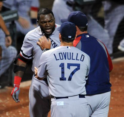Red Sox designated hitter David Ortiz is held back by bench coach Torey Lovullo and manager John Farrell.